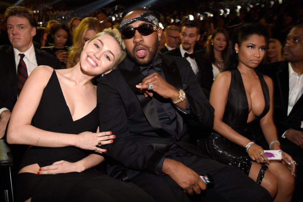 miley cyrus wears black dress and rests her head on music producer mike will's shoulder mike wills wears all black suit with bandana on his head and sunglasses nicki minaj sits next to mike wills in a low cut black dress at the grammys
