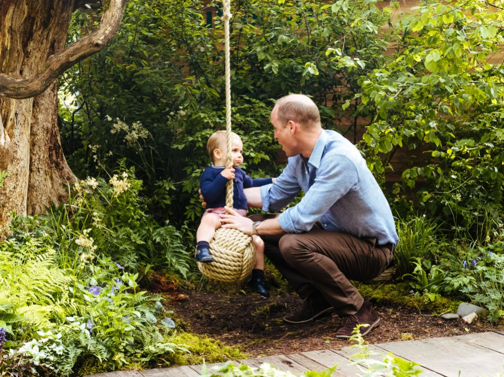 prince william wears blue shirt and black pants while son louis sits on a swing wearing a navy blue sweater
