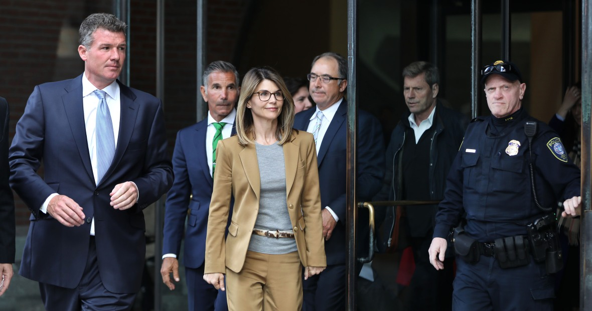 Lori Loughlin Wearing a Brown Suit in Boston With Her Husband Mossimo Giannulli Behind Her