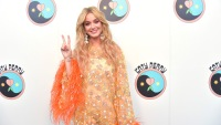 Katy Perry Wearing a Yellow and Orange Outfit and She Is Throwing Up a Peace Sign
