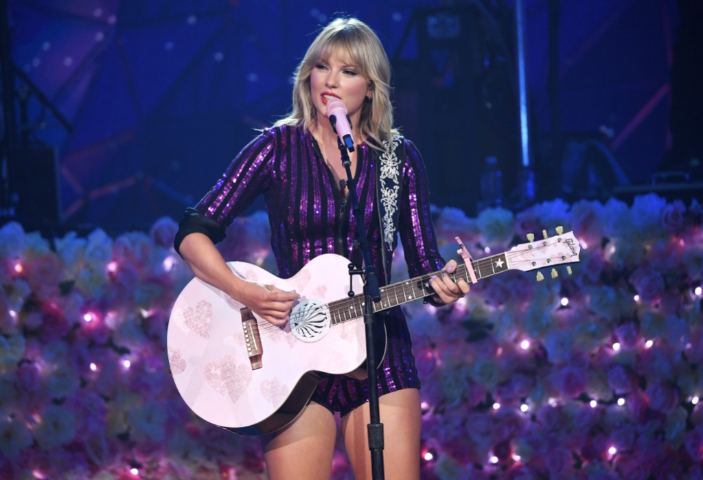 Taylor Swift Wearing a Purple Outfit With a Pink Guitar