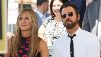 Jennifer Aniston Wearing a Black Dress With Red on It With Justin Theroux Wearing a White Shirt With Sunglasses