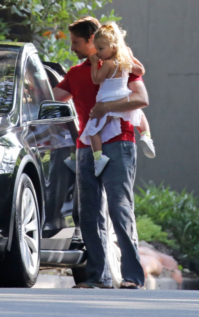 Bradley Cooper Holding His Daughter Wearing a Red Shirt
