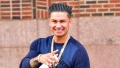 Pauly D Wearing a Blue Sweater With a Chain Around His Neck