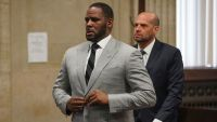 R. Kelly Adjusts Suit Jacket Button in Court
