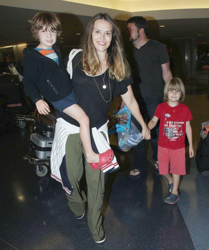 Brooke Mueller Wearing a Black Shirt Holding Her Son's Hands