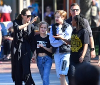 angelina jolie wears all black, daughter vivienne wears black t shirt and jeans, daughter shiloh wears a black puffy vest and a long sleeved gray sweatshirt with matching gray shorts, daughter zahara wears black t shirt and jeans and son knox wears black and white baseball tee with jeans while out at disney