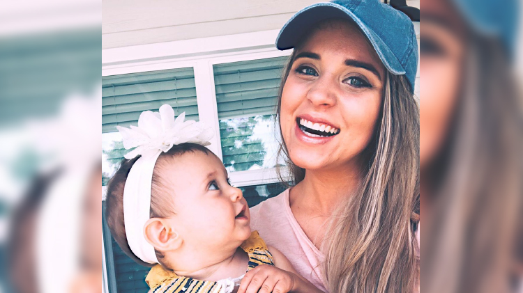 jinger duggar wears pink shirt and denim baseball cap while holding daughter felicity who is wearing a white floral headband jinger duggar coffee la instagram