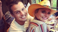 miranda lambert and her husband cuddle up in cute photo brendan wearing a white t shirt and miranda wearing a colorful striped dress and a straw hat while they celebrated her parents anniversary
