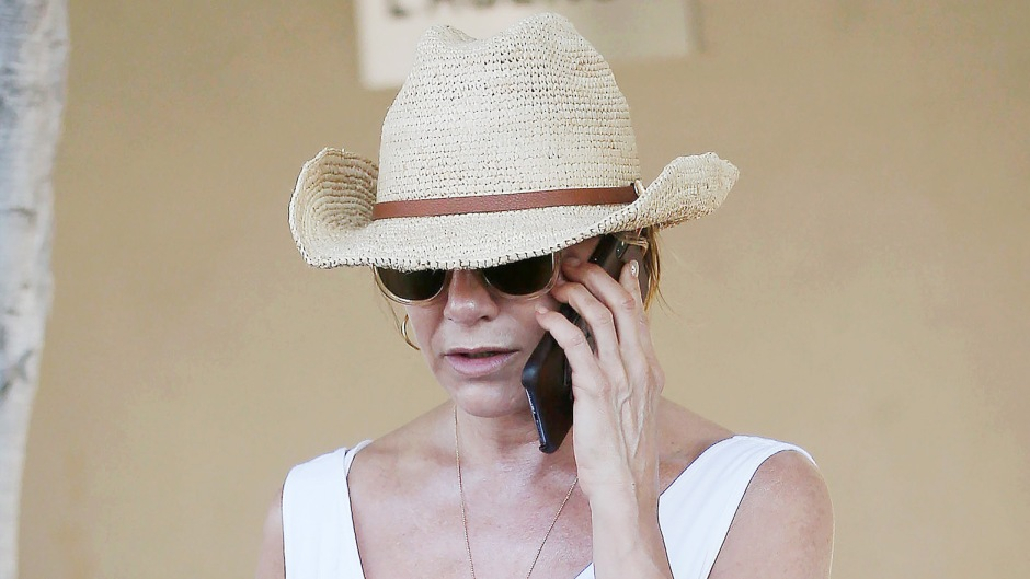 Jennifer Aniston Wearing White on Her Phone With a Hat