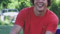 Christian Andreacchio Smiles While Sitting Outside in Red Shirt