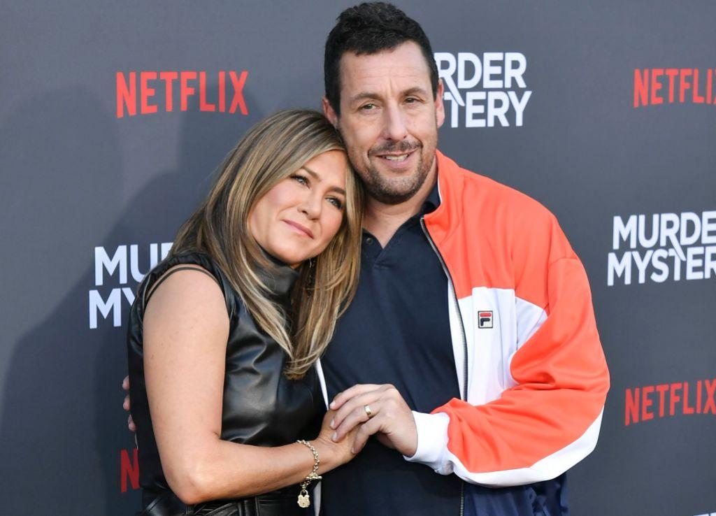 Jennifer Aniston Wearing a Black Dress With Her Arms Around Adam Sandler in an Orange Sweatshirt