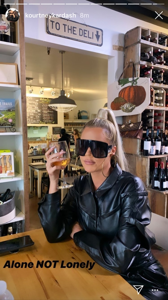 Khloe Kardashian Sitting at Table Drinking Alcohol Indoor Restaurant With Wine Collection and Deli