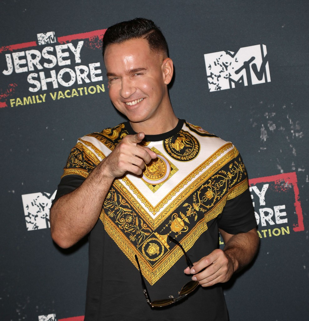 Mike the situation Pointing at the Camera Wearing a Yellow and Black Shirt
