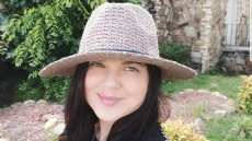 amy duggar smiling at camera with hat on