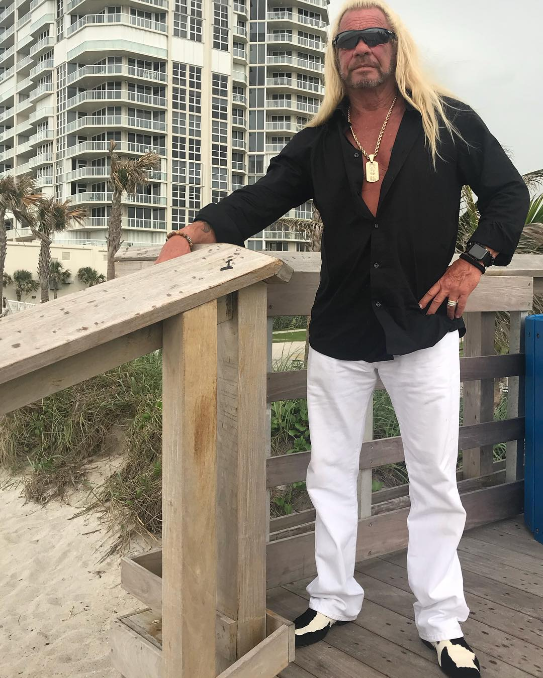 duane dog chapman standing on a deck on the beach
