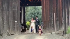 jackson and ember roloff hold 'just married' signs at their uncle jacob and aunt isabel's wedding