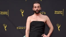 queer eye star jonathan van ness wears a black strapless mini dress with large teal bow accent on the 2019 Creative Arts Emmys red carpet queer eye jonathan van ness hiv positive