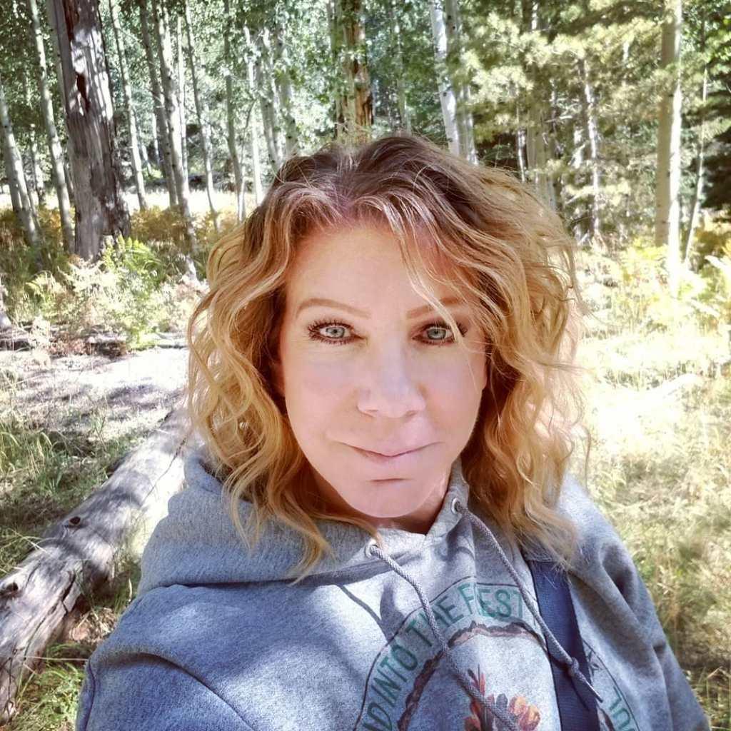 meri brown selfie in the woods wearing a hoodie