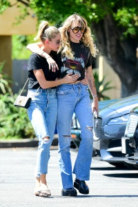 miley cyrus and kaitlynn carter both wear blue jeans and black t-shirts as they pack on the pda during out in los angeles