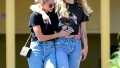 miley cyrus and kaitlynn carter both wear blue jeans and black t-shirts as they pack on the pda during out in los angeles miley cyrus and katilynn carter pack on pda