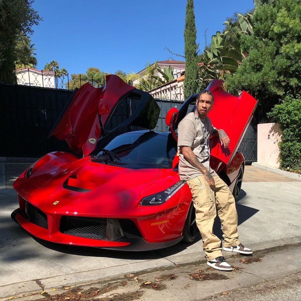 Tyga Standing in Front of a Red Car