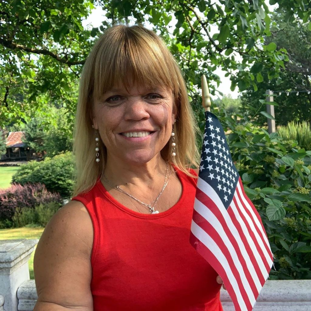 amy roloff holding flag and smiling