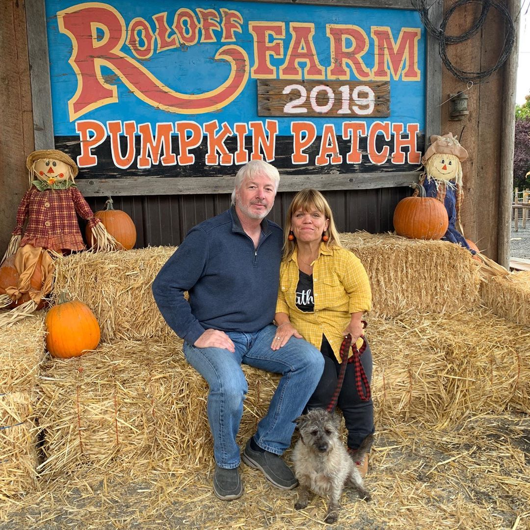 amy roloff with boyfriend chris marek and dog in front of roloff farm sign