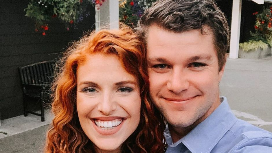 audrey and jeremy roloff smiling at camera with flowers behind them