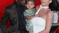 kylie jenner wears a white dress and travis scott wears a black button down shirt underneath a brown suit and stormi webster wears a matching bright green camouflage matching shirt and pants set kylie jenner and travis scott are coparenting stormi