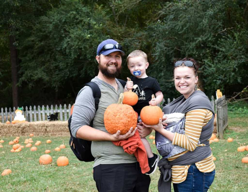 maddie brown and caleb brush holding their kids and pumpkins
