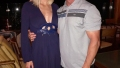 meghan king edmonds wears blue long sleeve deep v neck flowy mini dress jim edmonds wears a gray polo shirt with black top stripes and black shorts
