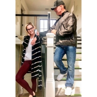 meghan king edmonds wears wine stirrup leggings with white t shirt and black and white sweater while jim edmonds wears black nike hat, brown windbreaker jacket, jeans and white sneakers