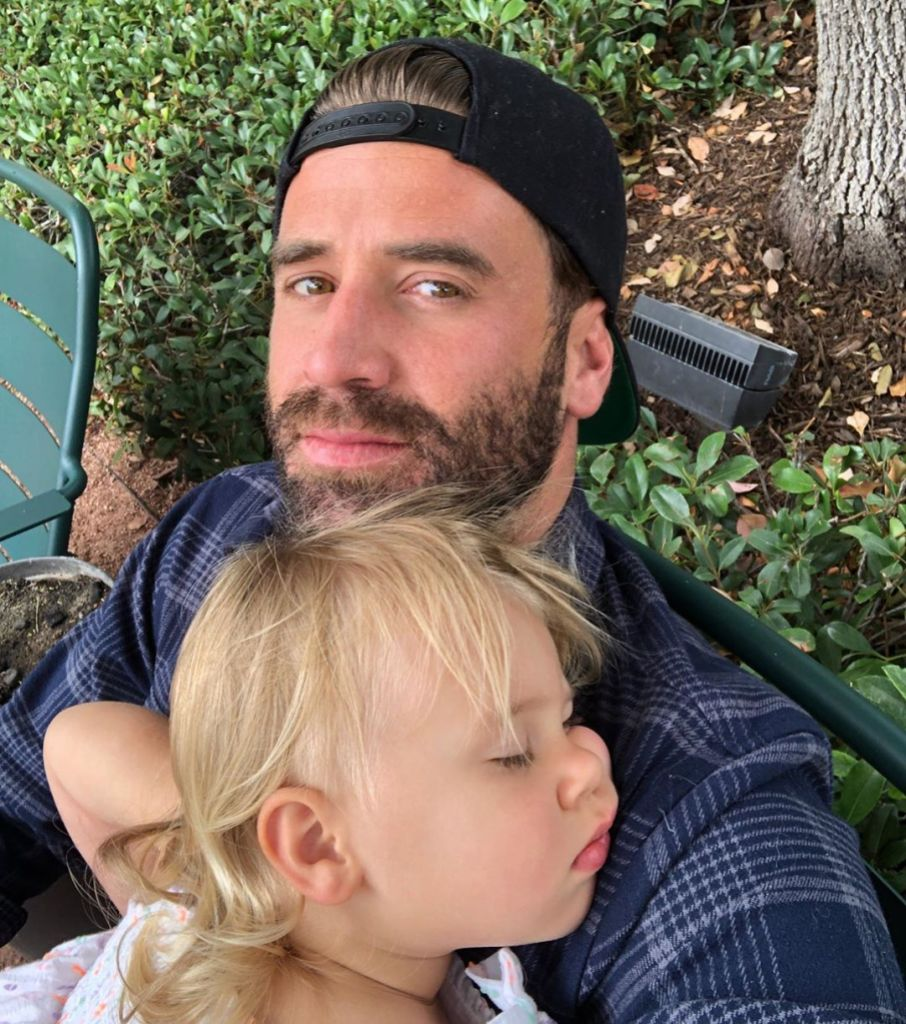 Jason Wahler Wearing a Hat With His Daughter Sleeping on His Shoulder