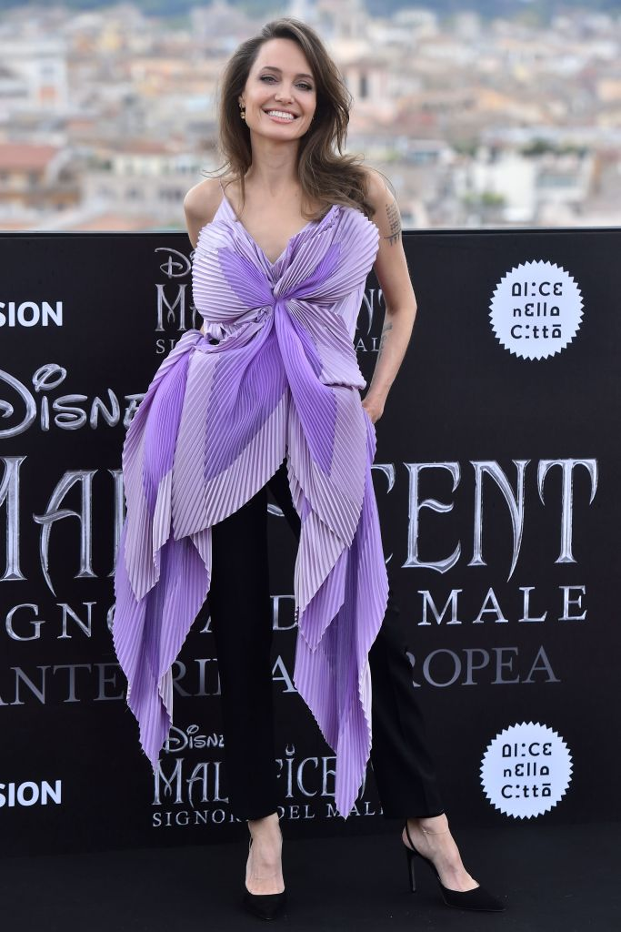 Angelina Jolie Wearing a Purple Top With Black Pants
