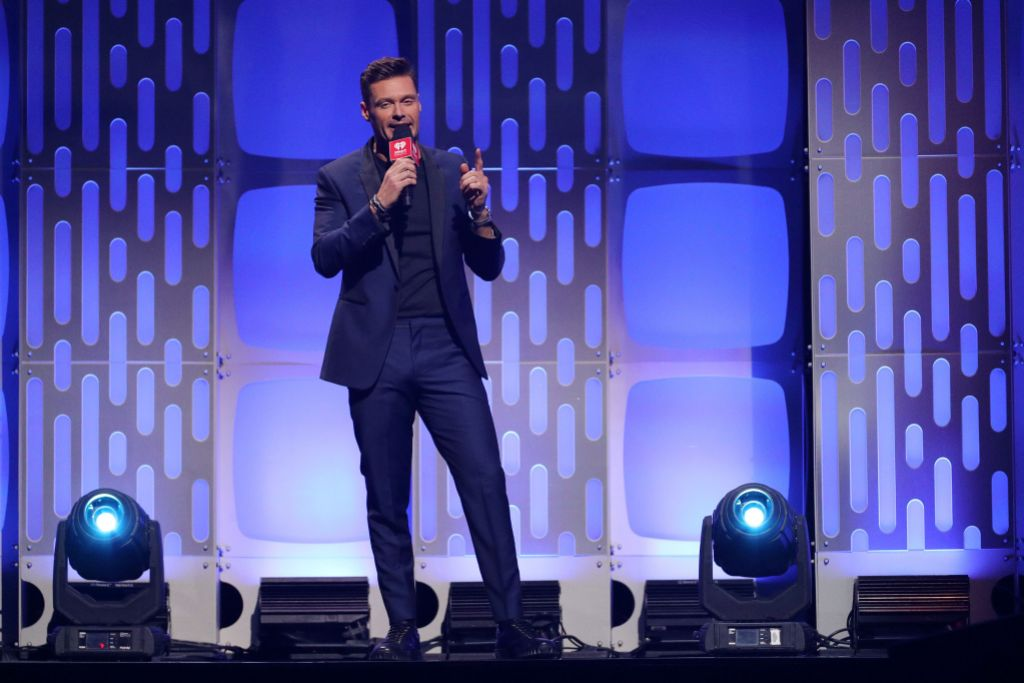 Ryan Seacrest with a Microphone on Stage