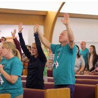 mackenzie mckee's parents worshipping in a church