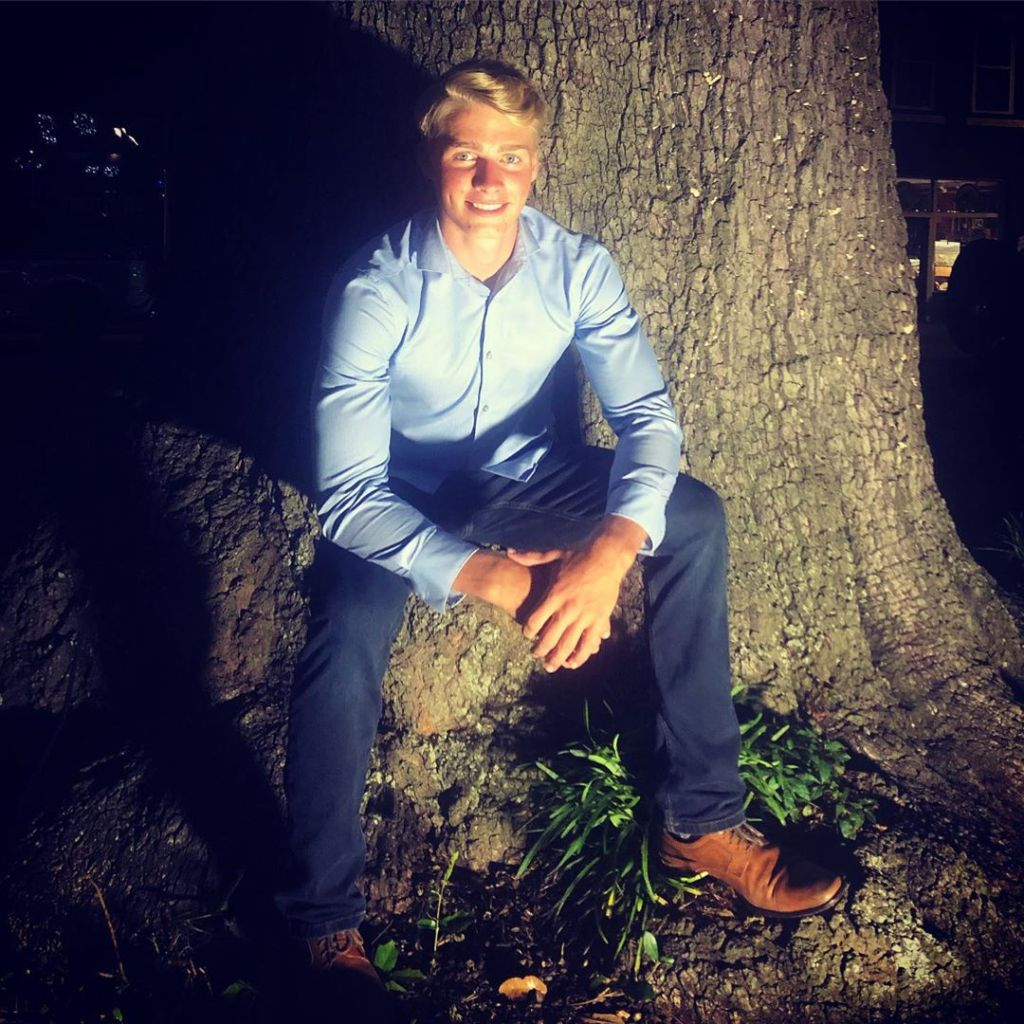 micah plath sitting on a tree in the dark