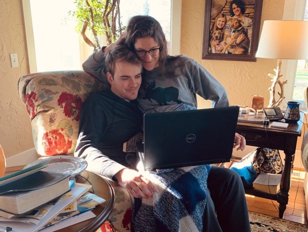 molly roloff sitting on joel silvius' lap while the look at a laptop