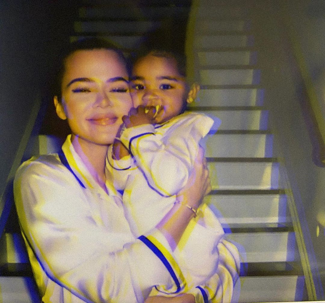 Khloe Kardashian Smiles and hugs Daughter True in White Silk Pajamas