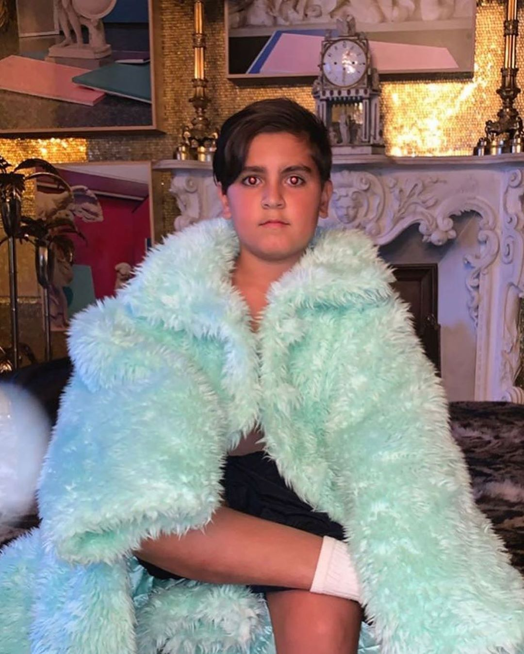 Mason Disick Sits Seriously Wrapped in Turquoise Coat