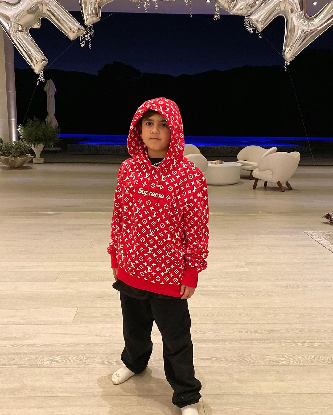 Mason Disick Stands in a Red Hoodie and Black Sweats