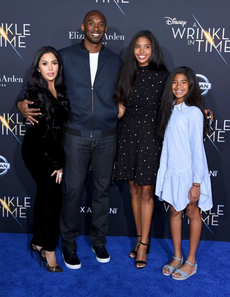 Kobe Bryan Wears Blue Suit Smiling With Wife Vanessa in Black Dress and Daughters Gianna and Natalia
