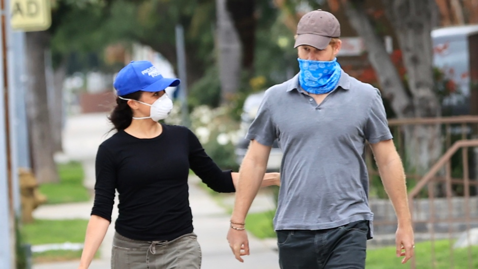 Meghan Markle Wears Army Green Joggers and Black Tshirt and Looks At Prince Harry Wearing Blue Mask and Baseball hat