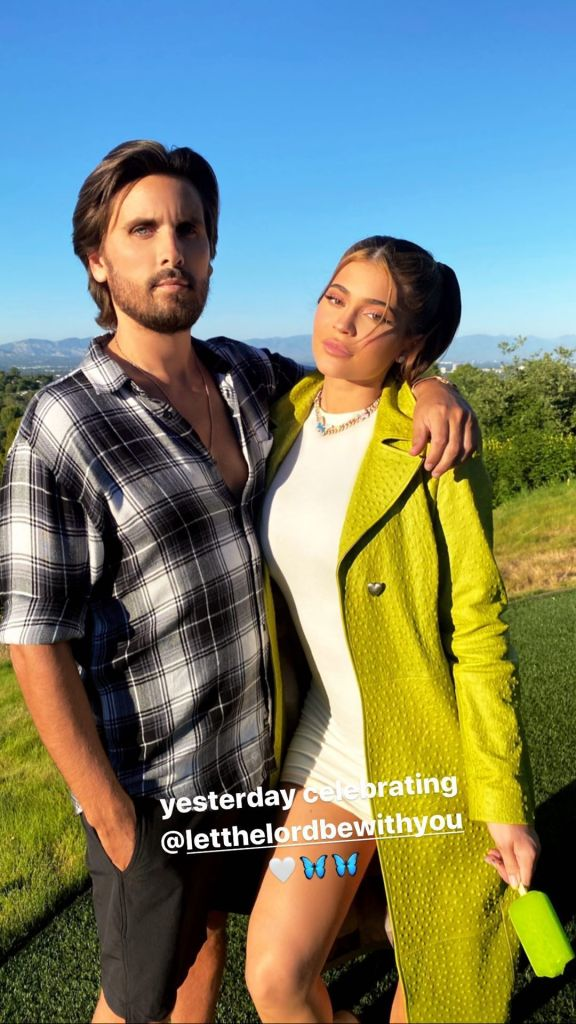 Kylie Jenner Wears white Dress and Long Green Coat With Hair in Pigtails With Scott Disick in Plaid Shirt and Shorts